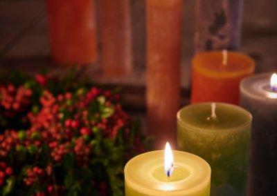 Bunte Kerzen mit Beerenkranz