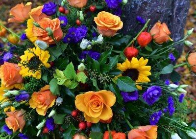 Farbenfroh Orange Und Blau Gesteck Mit Rosen
